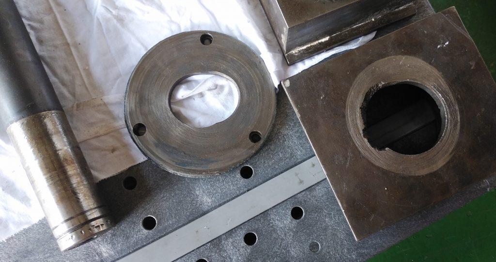 変形した部品の写真。正円であるはずの穴が完全に楕円形に変形しています。
