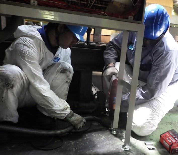 架台を床に固定している作業。