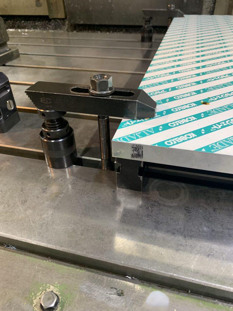 マシニングセンタに付随している、スライドするボルトを使い爪で材料を固定している例。アルミプレートを固定している状態(t20*600*600)。