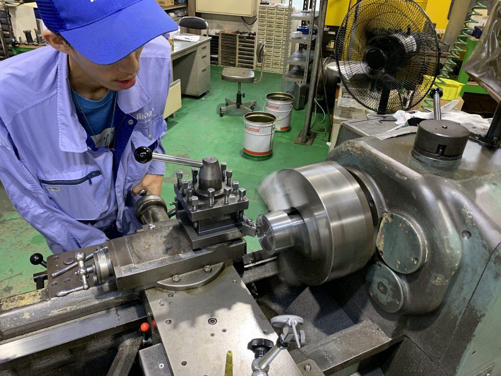 旋盤加工している様子の写真です。加工する金属が回転する装置に固定されて回転しているところに、刃を近づけて削る作業です。