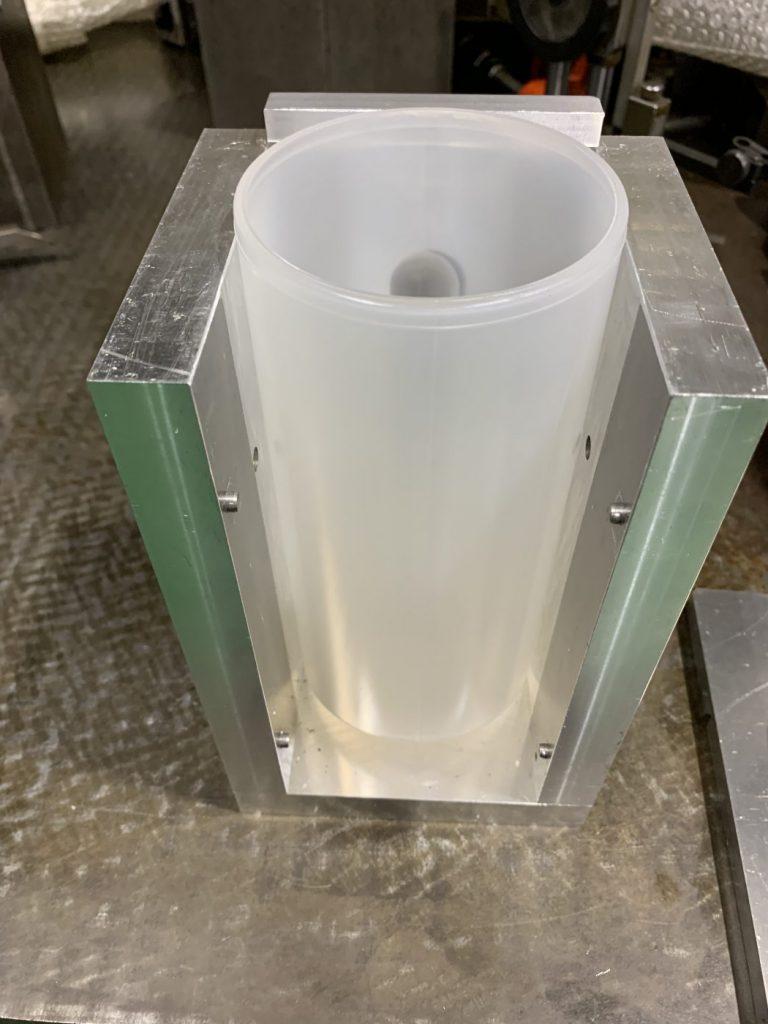 加工物を3方向から固定している写真。奥側に加工物のでっぱりがあり、固定する治具にはそのでっぱりに対応する穴が空いている。