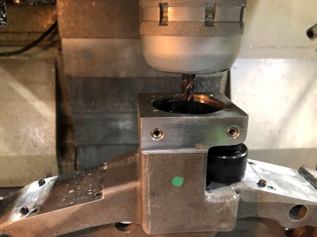 エンドミルを使って加工しているところの写真です。元々あいていた穴の中にドリルが挿入されている様子が分かります。