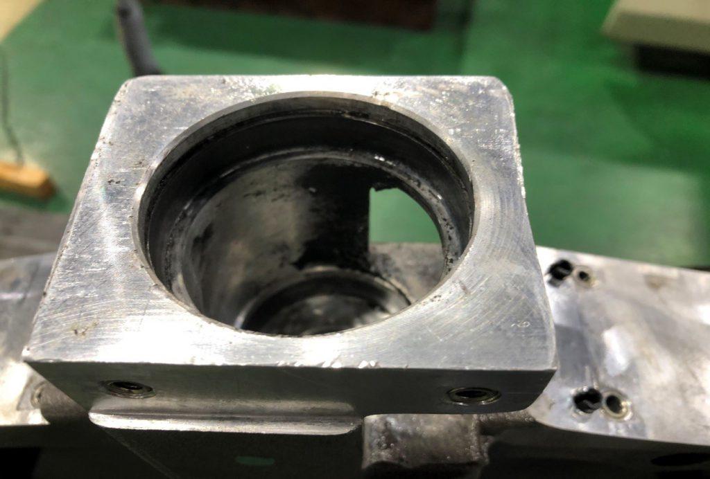 修理を依頼されたアルミ製の部品の写真です。表面に傷が見られ、使い込んでいる様子が見受けられます。