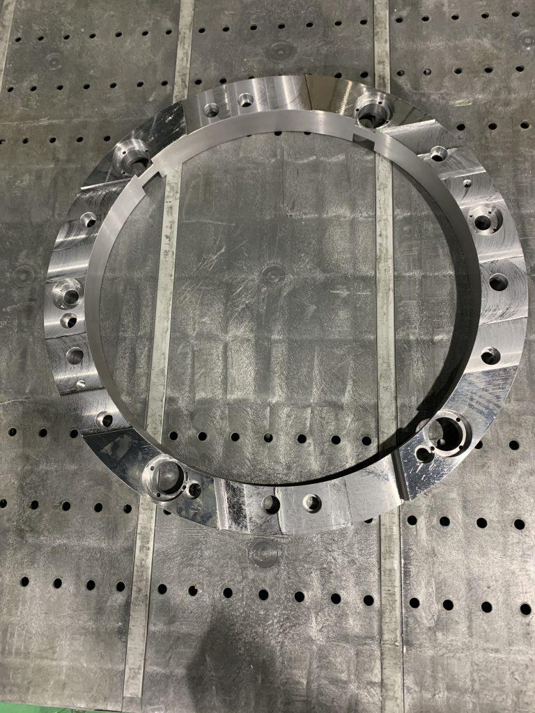 複合加工の一例の写真です。中心の穴の周囲に、大小さまざまな穴が空き、溝が彫られている複雑な形状の製品です。