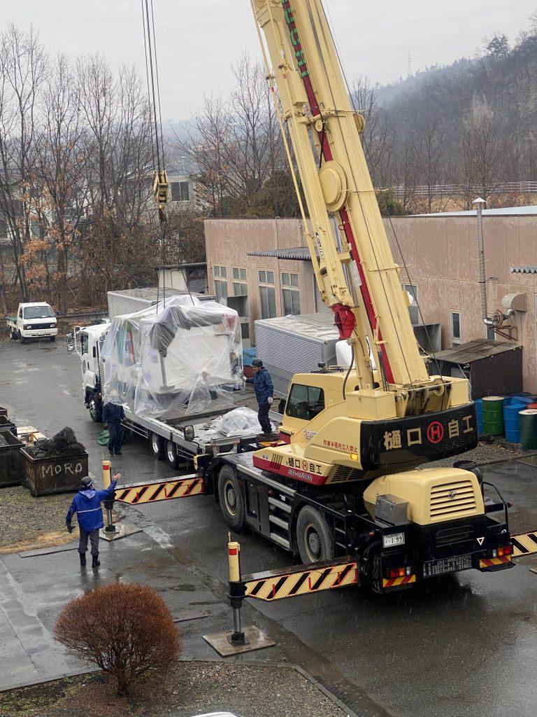 運搬業者様がトラックの荷台からクレーンを使って機械を下ろしているところです。機械はビニールに覆われていて、雨に濡れるのを防いでいます。