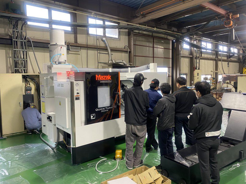 工場内に運び込まれた機械を社員が眺めています。
