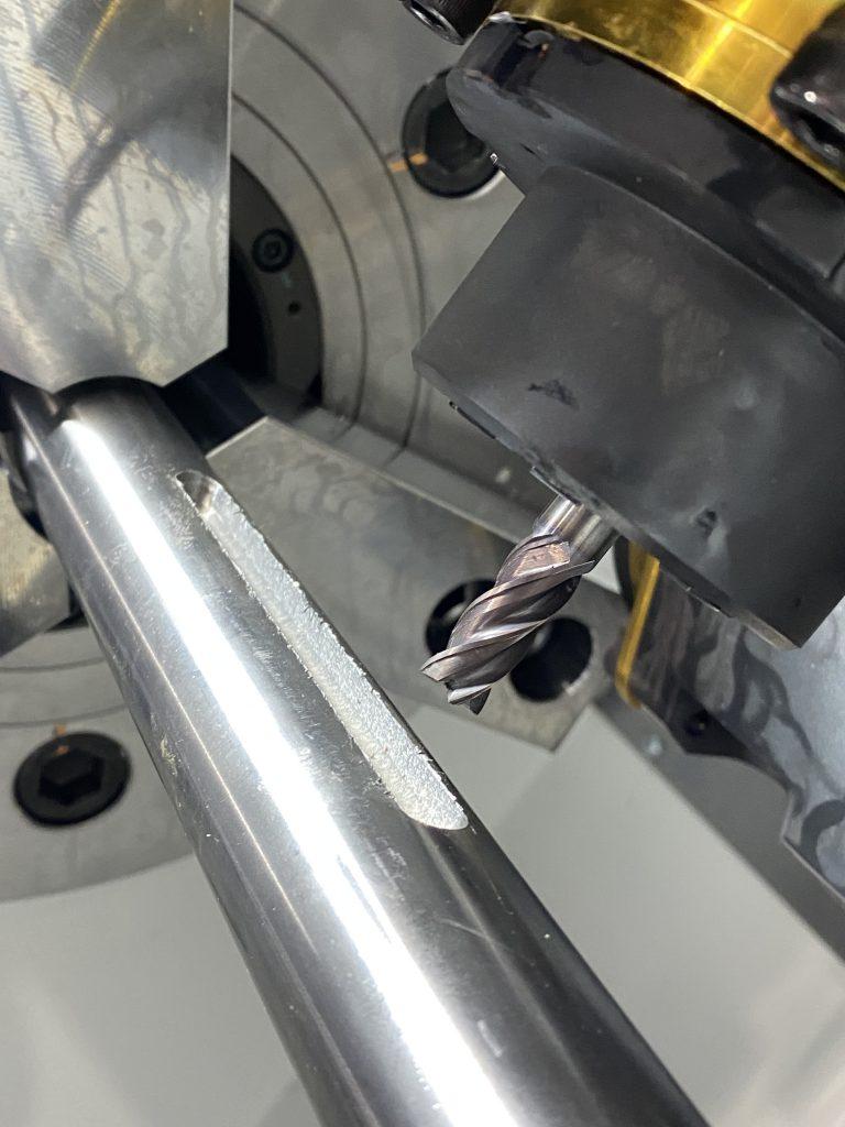 回転する機構の軸になる金属製品です。回転しながら動力を伝える際に、ひっかりになる部分がキーと呼ばれるものです。軸の側面に楕円形の溝が彫られている様子の写真です。