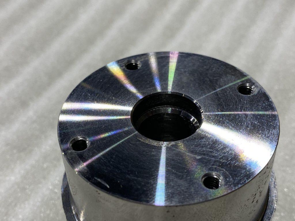 円筒形の金属の円の面に、中心に大きな穴が空き、円周に沿って4ヶ所小さな穴が空いている製品の写真です。