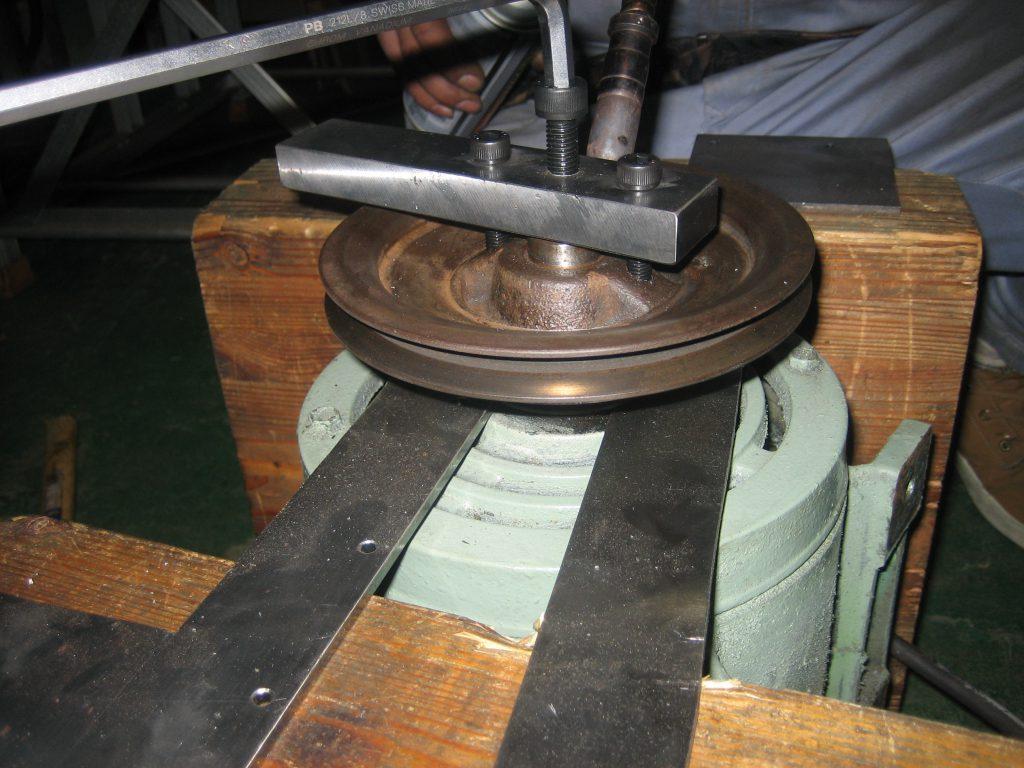 専用工具によるプーリー外し作業の様子の写真です。プーリーにタップ加工(穴あけ・ネジ山切)を行い、自作した工具を使って作業しています。