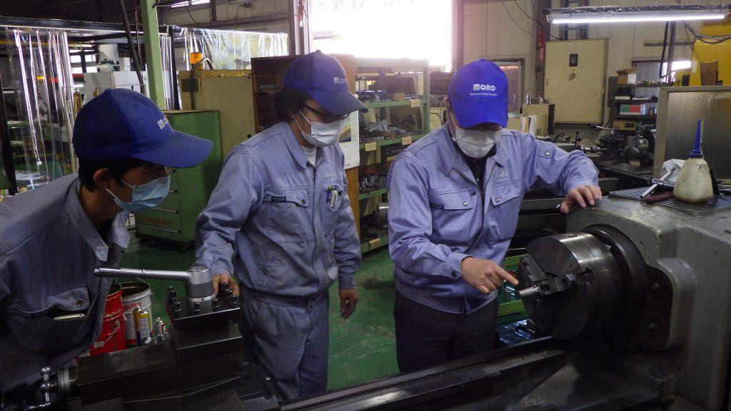 すり合わせ加工の説明をしているところの写真です。ベテラン技術者が若手2人に加工機の使い方を説明しています。