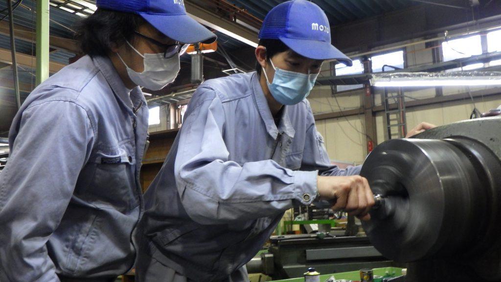 もう一人の若手技術者の作業を、先ほど指導を受けた若手技術者が見学しているところの写真です。