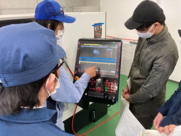機械に触れながらプログラムを説明しているところ