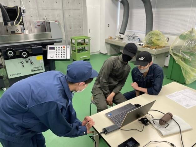 PCのモニターを使って茂呂製作所本社の様子を見ている学生さん