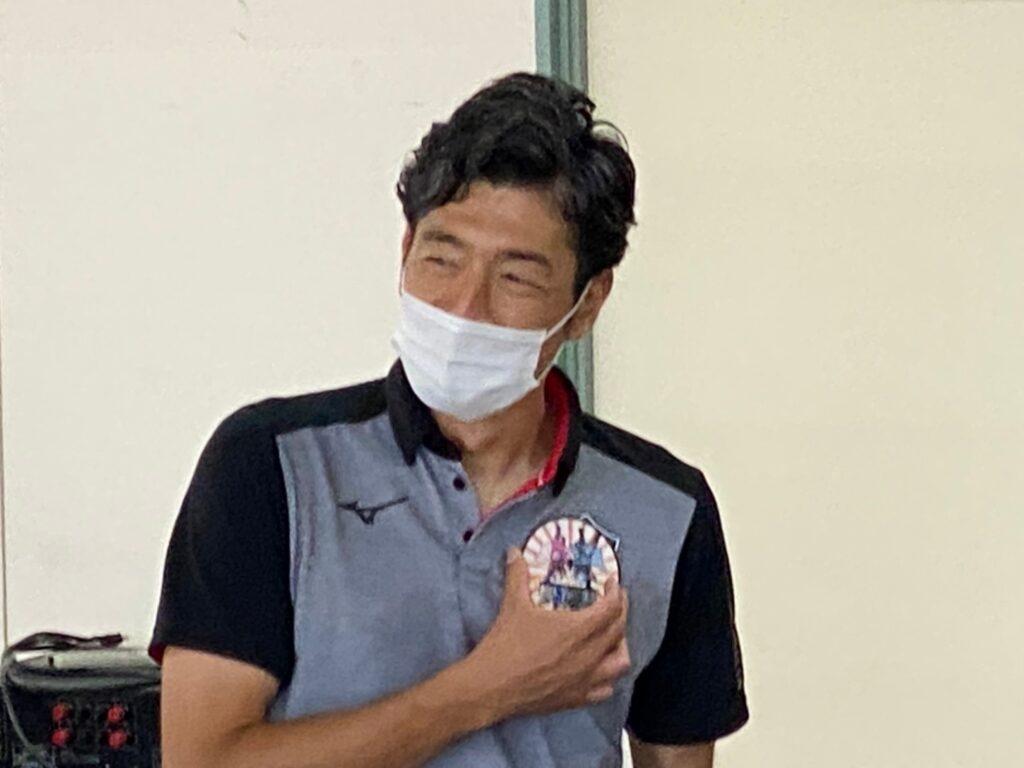 須藤大輔さんがメンテマンのワッペンを胸に当てているところ