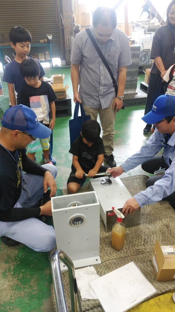 モーターの組み立てを子どもに指導しているところ