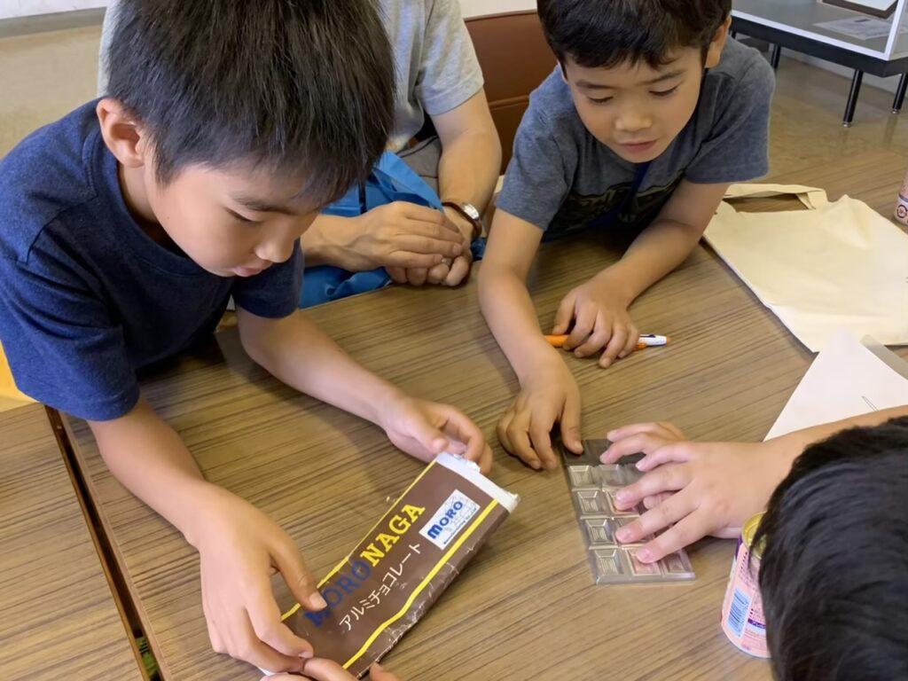 アルミで作られた、チョコレートそっくりの作品に興味を示している子供たち