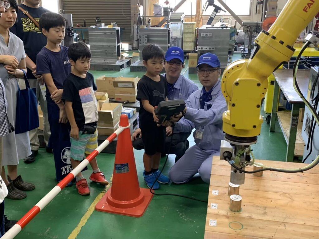産業用ロボットへのティーチングを子どもたちに指導しているところ