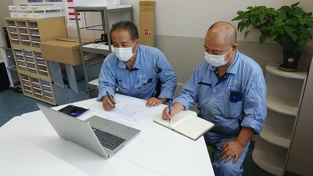 茂呂製作所の指導員2名がパソコンを通じて対応している様子